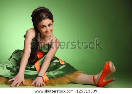 beautiful girl with a plait of hair on a green background - stock photo