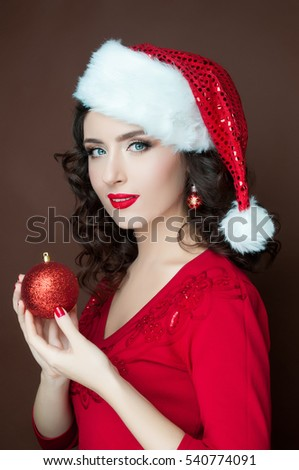 Beautiful girl with a red Christmas ball in hands in the hat of Santa Claus, New Year, Merry Christmas