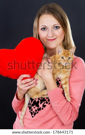 Beautiful girl with a red heart and a kitten - stock photo