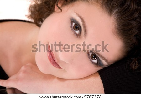 Beautiful girl with a serene smile resting on her arm - stock photo