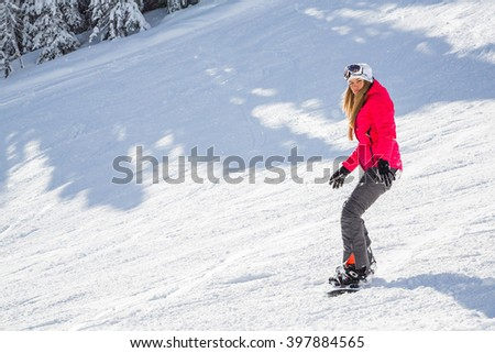 Beautiful girl with a snowboard sliding down the mountains - stock photo