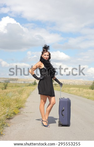 Beautiful girl with a suitcase on the road