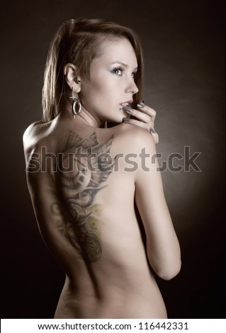 Beautiful girl with a tattoo on her back and piercings on a dark background - stock photo