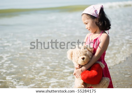 beautiful girl with a teddy bear at the beach - stock photo
