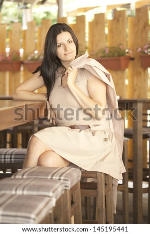 Beautiful girl with a topcoat sitting on a barstool at the sidebar - stock photo