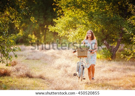 beautiful girl with a vintage bike in the park