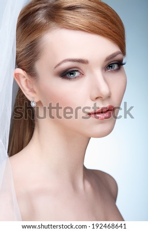 Beautiful girl with a white veill, isolated on a light - grey background, emotions, cosmetics