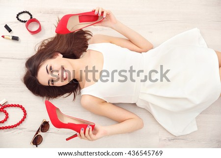 Beautiful girl with accessories lying on floor