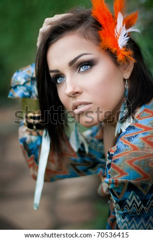 Beautiful girl with an orange feather in her hair - stock photo