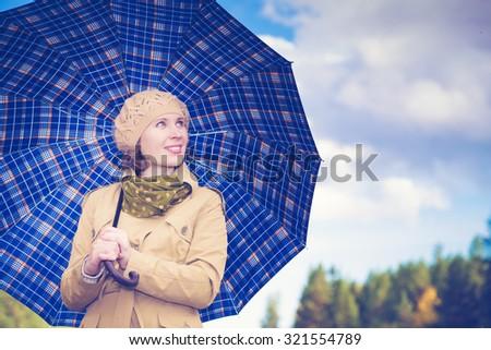 Beautiful girl with an umbrella autumn day. - stock photo