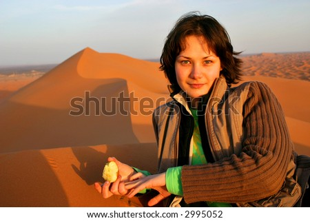 Beautiful girl with apple lying on the top of the sand dune in Sahara desert - stock photo