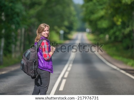 Beautiful girl with backpack walking on the road - stock photo