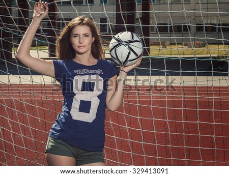 Beautiful girl with ball on the soccer field - stock photo