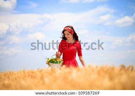 Beautiful Girl with basket walking across wheat field
