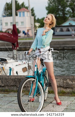 Beautiful girl with bicycle on the sea and yacht background. Outdoors, lifestyle