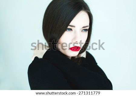 beautiful girl with black hair and red lips posing in the blue room - stock photo