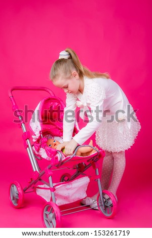 beautiful girl with blond hair lays the doll in the stroller - stock photo