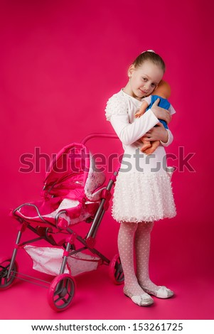 beautiful girl with blond hair swayed doll to sleep - stock photo