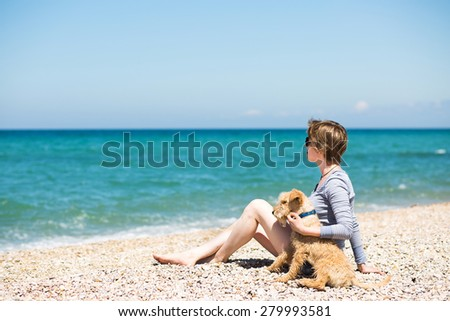 Beautiful girl with blonde hair in a blue blouse sitting on the beach with a dog - stock photo