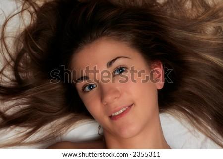 beautiful girl with blue eyes lying on white bedheet - stock photo