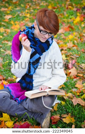 Beautiful girl with book in the autumn park - stock photo