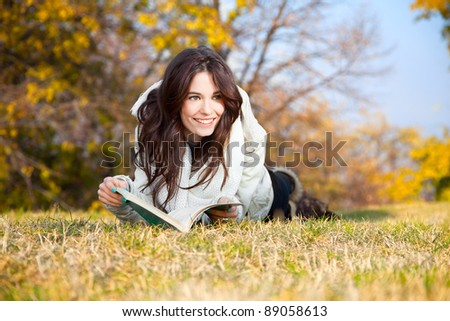 Beautiful girl with book lying on grass in the autumn colored park