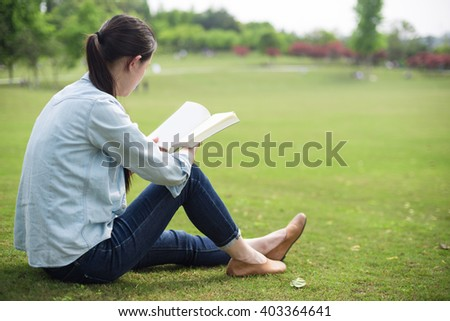 beautiful girl with book on the grass