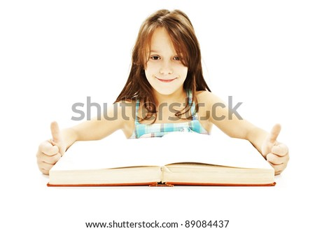 Beautiful girl with book on the table, showing OK sign. Isolated on white. - stock photo