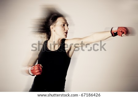 Beautiful girl with boxing gloves in motion - stock photo