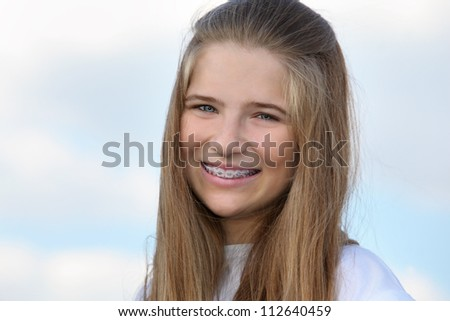 Beautiful girl with braces smiles at background of blue sky with clouds. - stock photo