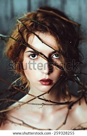 Beautiful girl with branch of grapes around her head. Spring