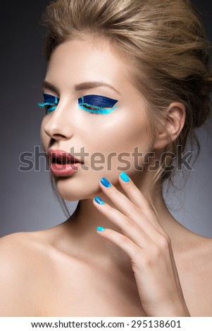 Beautiful girl with bright creative fashion makeup and blue nail polish. Art beauty design.