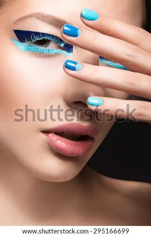 Beautiful girl with bright creative fashion makeup and blue nail polish. Art beauty design.  - stock photo