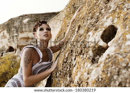 beautiful girl with bright makeup and tattoo near the rocks - stock photo