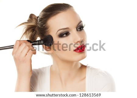 beautiful girl with bright makeup puts blush on white background