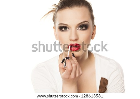 beautiful girl with bright makeup puts lip gloss on white background