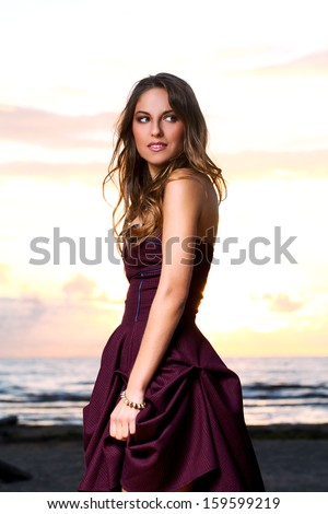 Beautiful girl with brown hair who is wearing a dark purple dress is posing at a beach