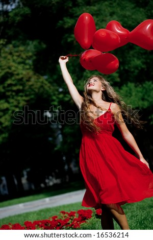 Beautiful girl with bunch of hearts outdoors - stock photo