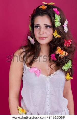 Beautiful girl with butterflies in hair poses in studio isolated on red
