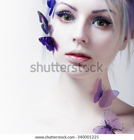Beautiful Girl With  Butterfly. Beauty Face. Creative Make up and colored lenses. - stock photo