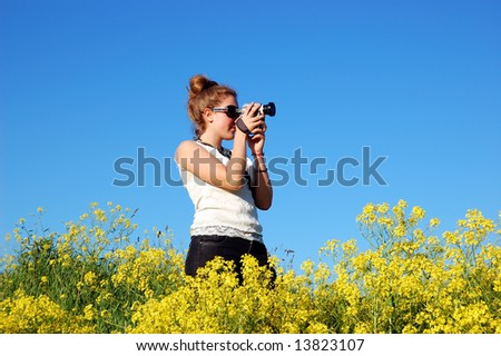 Beautiful girl with camera over a blue sky - stock photo