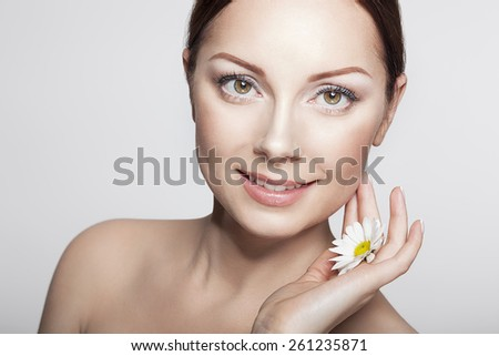 Beautiful Girl With Camomile Flowers.Close-up Beauty Woman Face. Perfect Skin.Body care. Professional Make-up. - stock photo