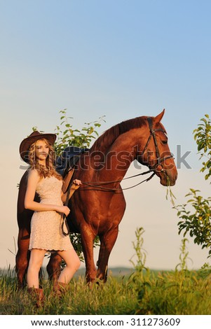 Beautiful girl with chestnut horse in evening field - stock photo
