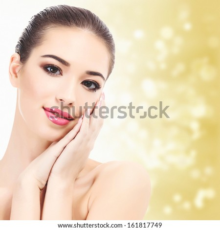 Beautiful girl with clean fresh skin, yellow background with blurred lights