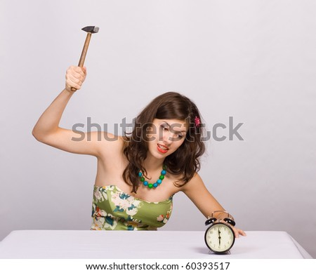 Beautiful girl with clock and hammer a over white background - stock photo