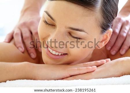 Beautiful girl with closed eyes having massage - stock photo