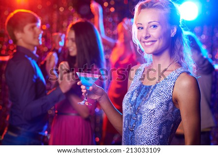 Beautiful girl with cocktail looking at camera at party - stock photo