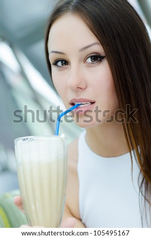Beautiful girl with creamy coffee drink in cafe