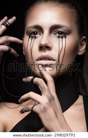Beautiful girl with creative make-up in Gothic style and the threads of eyes. Art beauty face. Picture taken in the studio on a black background. - stock photo