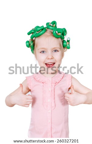 Beautiful girl with curlers on her head and smiling - stock photo